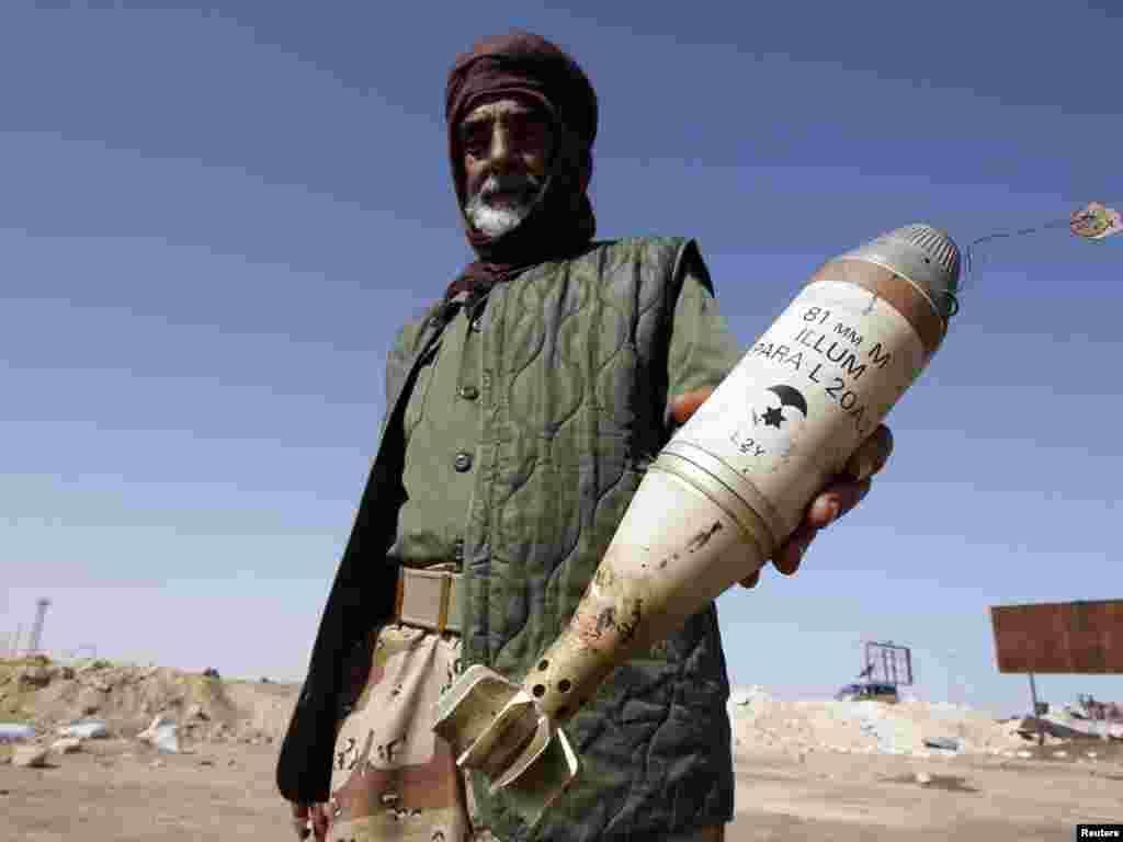 Лівійський повстанець демонструє 81-міліметрову освітлювальну міну, 14 квітня. Для успіху операції коаліції у Лівії НАТО бракує військових засобів. Їх наразі не можуть надати 34 держави, що беруть у ній участь. Каддафі приховує свою важку військову техніку в густонаселених пунктах, а це значно ускладнює місію НАТО. Тож для цілеспрямованих атак альянсу потрібні додаткові літаки з високотехнологічним обладнанням. Photo by Amr Abdallah Dalsh for REUTERS