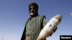 Бунтовник држи ракета за која тврди дека ја испукале вооружените лојалисти на лидерот Муамар Гадафи