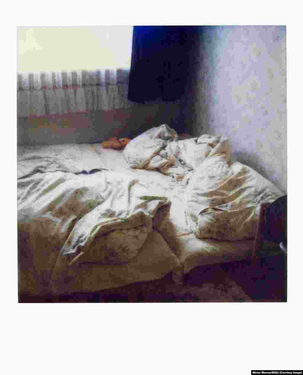 An instant photo of a bed in an empty apartment. When conducting secret apartment searches, such images were taken to help gloved Stasi agents restore things in time for the unsuspecting apartment owner's return.