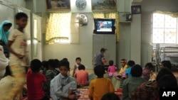 Дети смотрят телевизор в благотворительном центре в Карачи. Июль 2013 года.