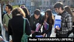 სტუდენტებს Transparency International Georgia-ს გამოცემულ ბუკლეტებს ურიგებენ
