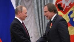 Владимир Путин награждает Сергея Ролдугина орденом Александра Невского за заслуги в подготовке и проведении гуманитарных внешнеполитических акций. Москва, Кремль, 22 сентября 2016 года