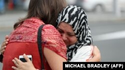 Residents hug after paying respects at a mosque in Auckland, New Zealand, following the attacks in Christchurch.