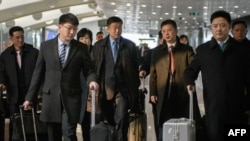A man understood to be North Korean nuclear envoy Kim Hyok Chol (center, blue tie) at Beijing international airport on February 19