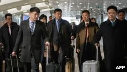 Ким Ҳёк Чхол дар акс дар миёна бо гарданбанди кабуд аст
