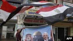 Palestine -- A vendor displays a poster of Hamas leader in the Gaza Strip Ismail Haniya (L) and President and Fatah head Mahmud Abbas in front of his shop in Gaza City, 28Apr2011