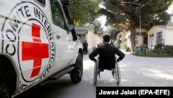 An Afghan man passes a van owned by the Red Cross in Kabul in October 2017.