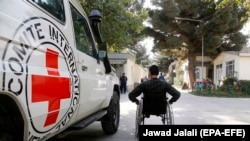 FILE: An Afghan handicapped man passes by a logo of ICRC in the pediatric center of the International Committee of the Red Cross (ICRC) in Kabul on October 10.