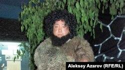"""Археолог Жанболат Казанбаев имитирует человека каменного века во время """"Ночи в музее"""". Алматы, 16 мая 2014 года."""