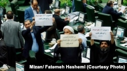 MPs opposing transparency laws holding slogans in parliament on October 07, 2018.