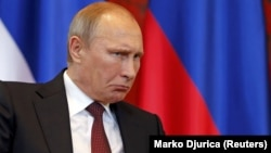 Arxiv fotosu: Prezident Vladimir Putin Serbiyada həmkarı ilə görüşdə onun çıxışına reaksiya verir. 16 oktyabr 2014