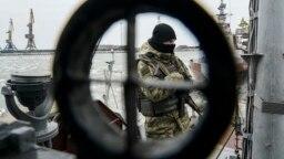 Militar ucrainean pe o vedetă de coastă ancorată în Mariupol.