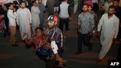 Чоловік несе до лікарні пораненого через вибух хлопчика, Лагор, Пакистан, 27 березня 2016 року