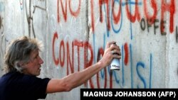 راجر واترز در حال گرافیتی کشیدن بر دیوار حائل اسرائیل در شهرک غرب بیت لحم، یک روز قبل از کنسرت در نزدیکی تل آویو، در ژوئن ۲۰۰۶