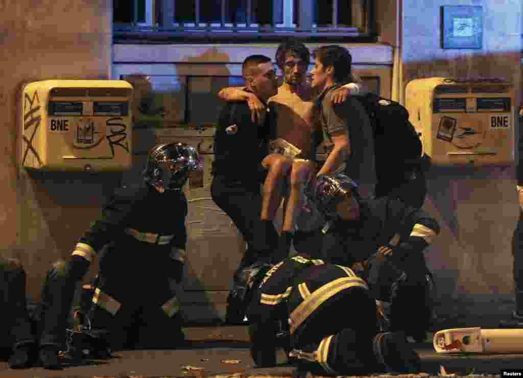 French fire brigade members aid an injured man near the Bataclan concert hall following the fatal shootings in Paris, France.