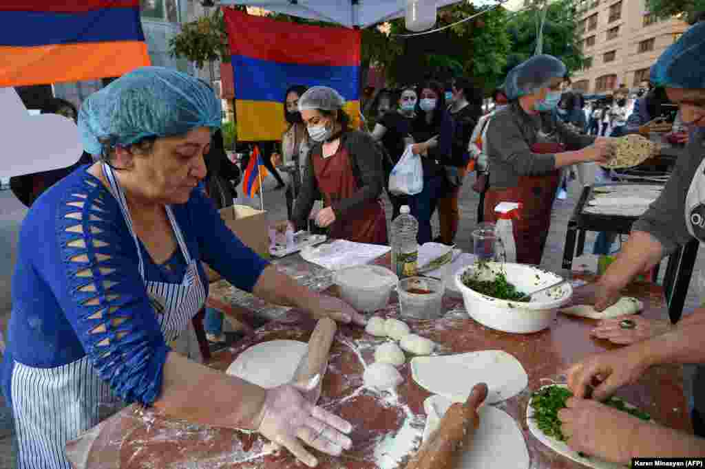 Refugees who fled the Nagorno-Karabakh region make jingalov hats-- traditional flatbreads stuffed with herbs, in central Yerevan on October 26.