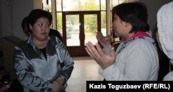 Назгуль Смагулова (слева), начальник отдела социальной сферы акимата Турксибского района Алматы, говорит с погорельцами.