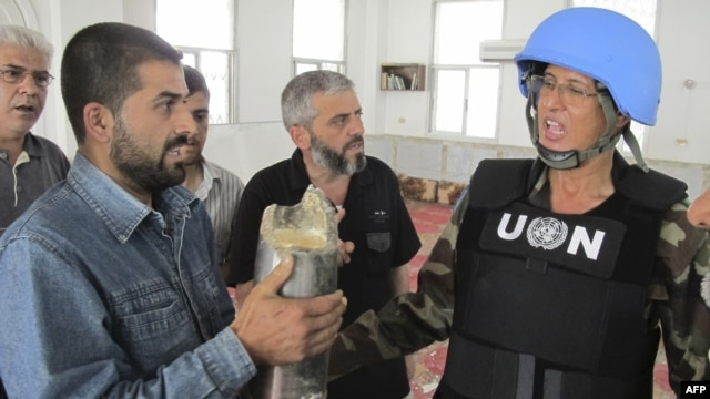 A Syrian resident shows a shell to a United Nations observer in the Talbisah area in Homs on June 11.