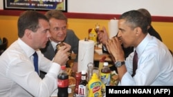 Medvedev watches as Obama digs in at Ray's Hell Burger.