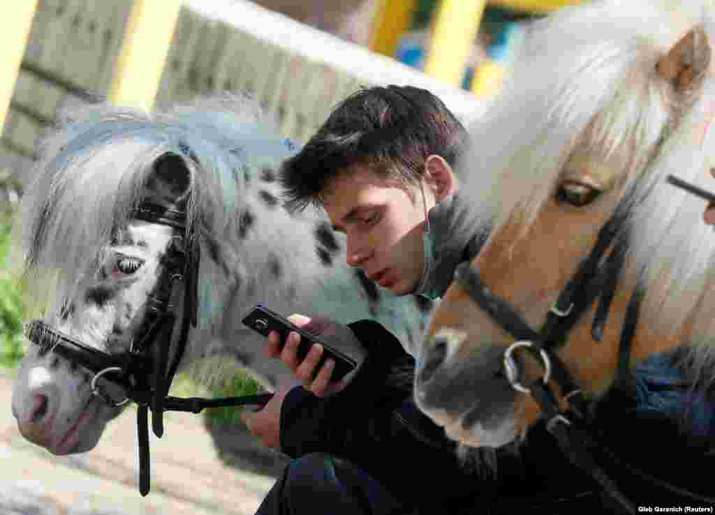 Ky person pret që fëmijët të kalërojnë ponit në një park në Kiev të Ukrainës.(Reuters/Gleb Garanich)
