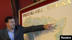 Bosnian Serb then-Prime Minister, and current president, Milorad Dodik shows his place of residence on a map of the Republic of Srpska during an interview with Reuters in Banja Luka, September 1, 2010