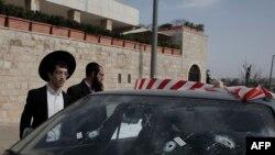Верующие евреи рядом с автомобилем, на лобовом стекле которого видны отверстия от пуль. Иерусалим, 9 марта 2016 года.