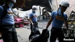 Пожарные вытаскивают тела погибших в пожаре на фабрике в Маниле