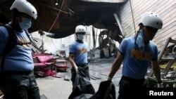 Филиппиндік құтқарушылар өртенген фабрикадан күйген адам денелерін әкетіп барады. Манила, 14 мамыр 2015 жыл.