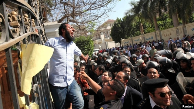 Egyptian police try to remove an Islamist protester chanting slogans from the fence of the Iranian ambassador's house during a protest against Iran in Cairo on April 5.