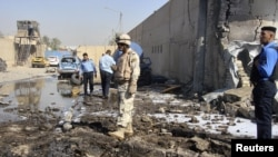 A soldier and policemen inspect the site of a bomb attack at a police station in Baghdad's Hurriyah district.