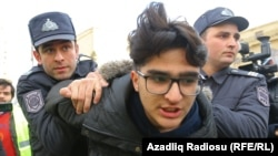 Police detain an activist in Baku ahead of the protest.