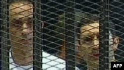 A TV grab shows Gamal (left) and Alaa Mubarak in a holding cell in the courtroom in the police academy on the outskirts of Cairo in August 2011.