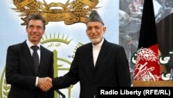 NATO Secretary-General Anders Fogh Rasmussen (left) Afghan President Hamid Karzai after the security handover to Afghan forces in Kabul on June 18.