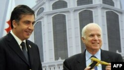 Saakashvili (left) presents the gold-plated pistol to McCain in Batumi.