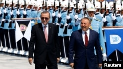 Turkish President Recep Tayyip Erdogan (left) and Kazakh President Nursultan Nazarbaev review an honor guard in Ankara on August 5.