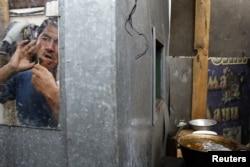 Трудовой мигрант бреется в своем жилище под Москвой. 6 июля 2011 года.