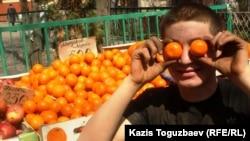 Торговец плодоовощной лавки в Алматы играет с мандаринами.