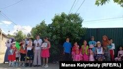 Қытай консулдығы маңында әке-шешесінің суретін ұстап тұрған балалар және олардың жақындары. Алматы, 1 маусым 2021 жыл.