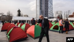 A man walks past tents set up by supporters of opposition parties in front of the Kosovo government building in Pristina on February 23
