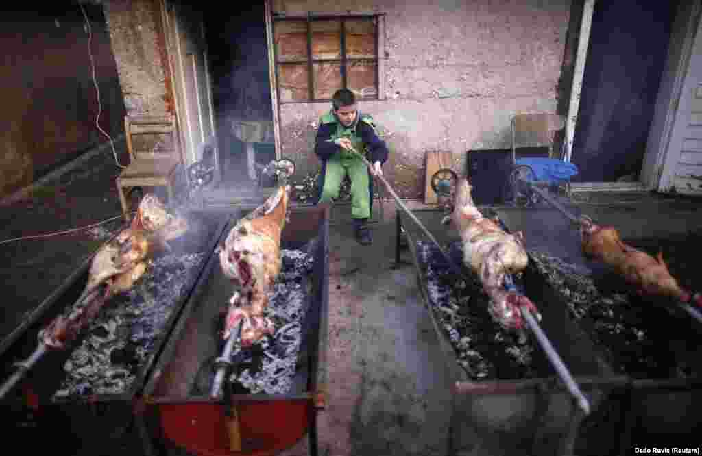 An ethnic Serb boy roasts lamb and pig in front of his home in the village of Vojkovici for a traditional Orthodox Christmas meal. (REUTERS/Dado Ruvic)