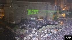 محتجون يتجمعون في ميدان التحرير بالقاهرة، فيما تظهر كلمة (مصر) بالإنكليزية مكتوبة بأشعة الليزر على بناية مجمع الدوائر الحكومية.