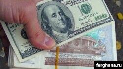 Банкнота номиналом в сто долларов США над банкнотой в тысячу узбекских сумов.