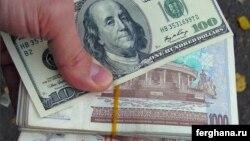 100-долларовая купюра и пачка узбекских сумов.