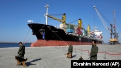 FILE: Security guards with their sniffer dogs patrol in front of a cargo ship during the inauguration ceremony of the newly built extension in the port of Chabahar in southeastern Iran (December 2017).