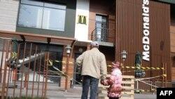 Чоловік з дитиною дивляться на закрите приміщення McDonald's у Сімферополі, 4 квітня 2014 року