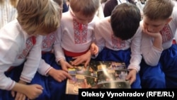 Дети рассматривают комикс «Приключения Никитки»
