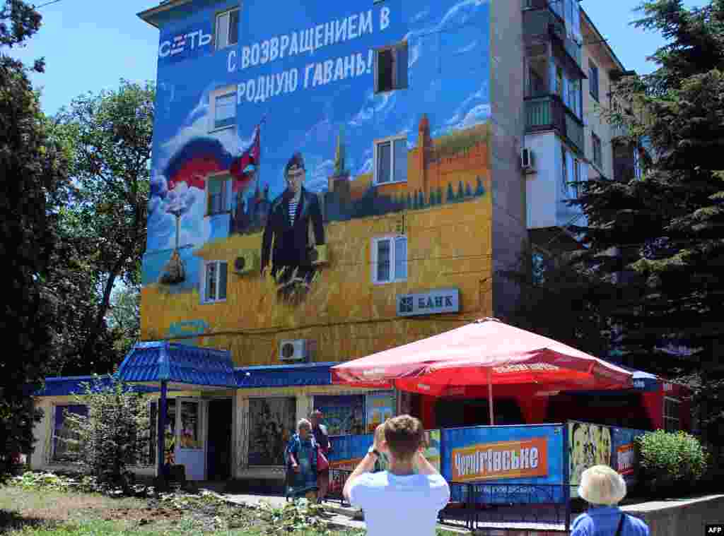 Pedestrians walk by a mural depicting Russian President Vladimir Putin dressed as a Russian Navy seaman, in the Crimean city of Sevastopol. (AFP Yury Lashov)