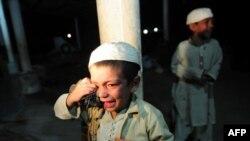 په کراچۍ کې د پولیس لخوا په یوه چاپه کې د ذکریا مدرسې یو وړوکی ماشوم طالب د راخوشي کېدو پر مهال ژاړي.۱۲ م ډسمبر ۲۰۱۱