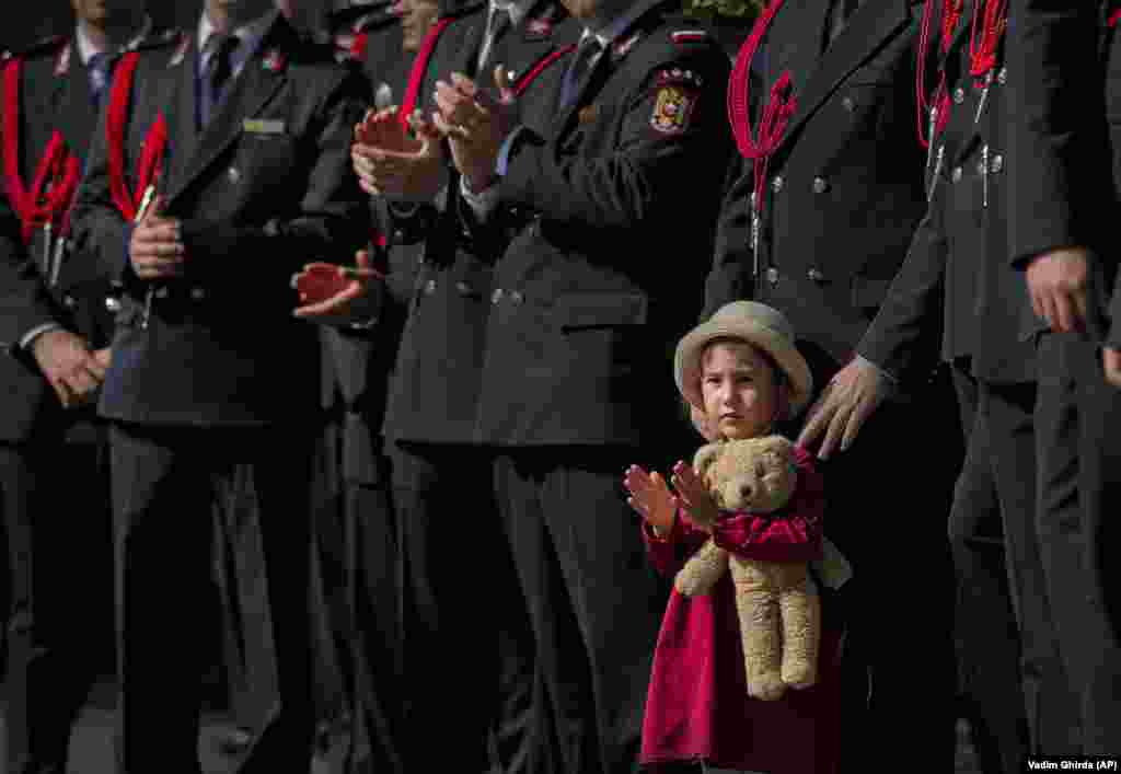 A girl holds a teddy bear while watching a military parade during festivities celebrating Romanian Firefighters Day in Bucharest on September 13. (AP/Vadim Ghirda)