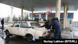 Участники акции протеста против дефицита бензина буксируют машину на АЗС в Алматинской области. 8 ноября 2014 года.